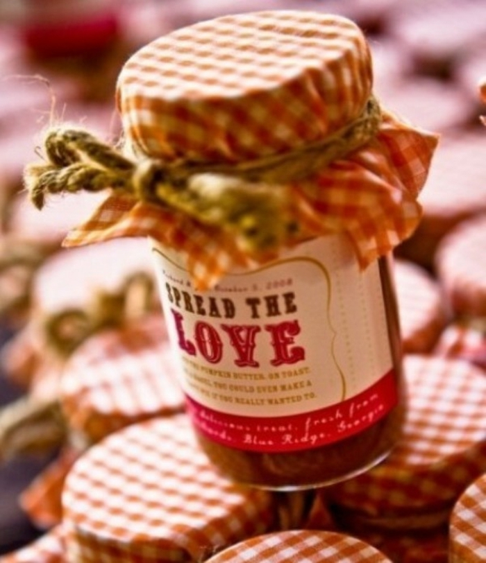 diy mason jar, close up of jar filled with red substance, covered in red and white checkered cloth, tied with a string, with a label saying spread the love, placed on top of many similar jars