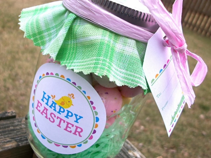 diy mason jar, with a round colorful label reading happy easter, covered with green and white plaid cloth, and containing colorful candy and easter grass
