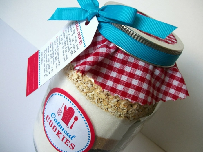 diy mason jar, clear jar filled with layers of ingredients, with a round label reading oatmeal cookies, covered with a red and white checkered cloth, and a teal ribbon