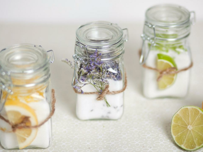decorating mason jars, three clear jars with snap glass lids, containing hand-made candles, and decorated either with orange or lime slices, or tiny violet flowers, tied around each jar with string