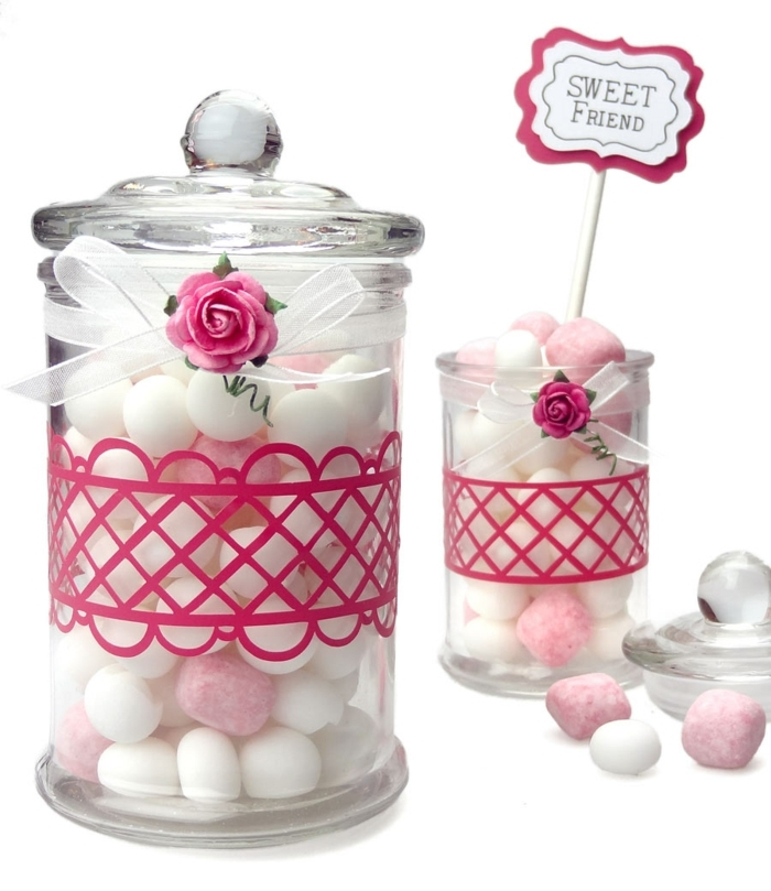 mason jar crafts, two clear jars with glass lids, filled with white and pink candy, decorated with pink details, white ribbons with bows, and tiny pink roses