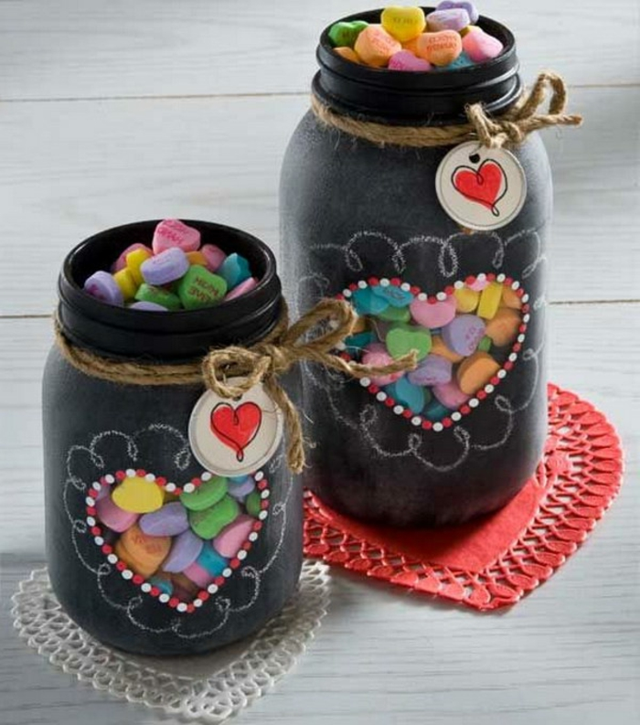 two differently sized jars, painted in black matte color, and decorated with white chalk, with heart-shaped windows, revealing colorful candy inside