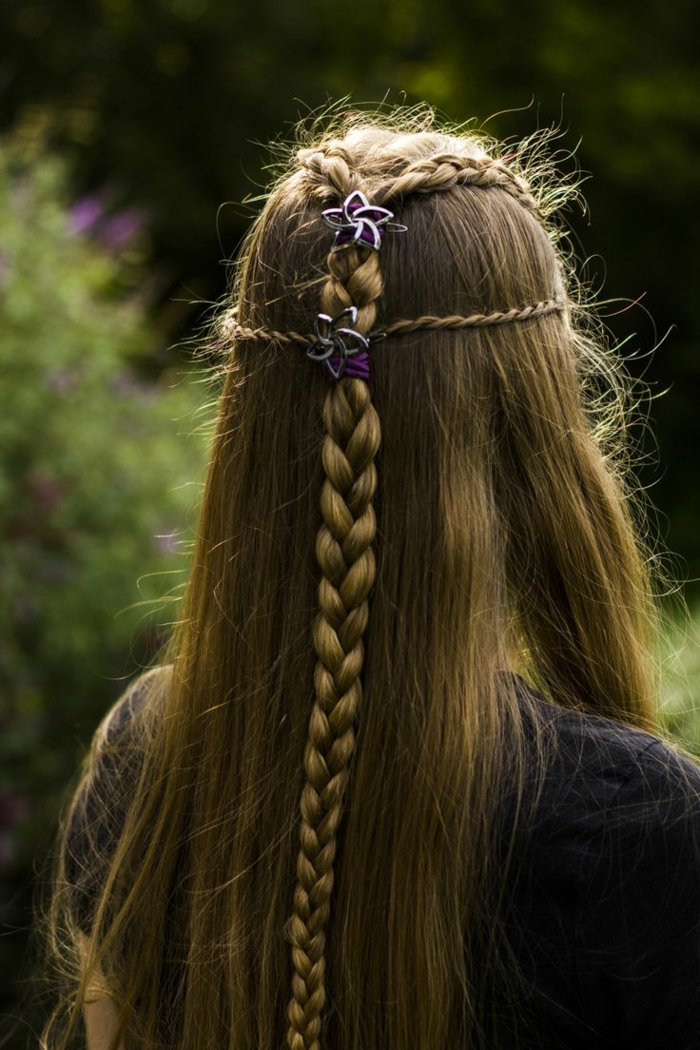 medieval braids, long straight dark blonde hair, with several small braids at the top, coming together in a bigger braid in the middle, and decorated with purple hairbands, and silver flowers