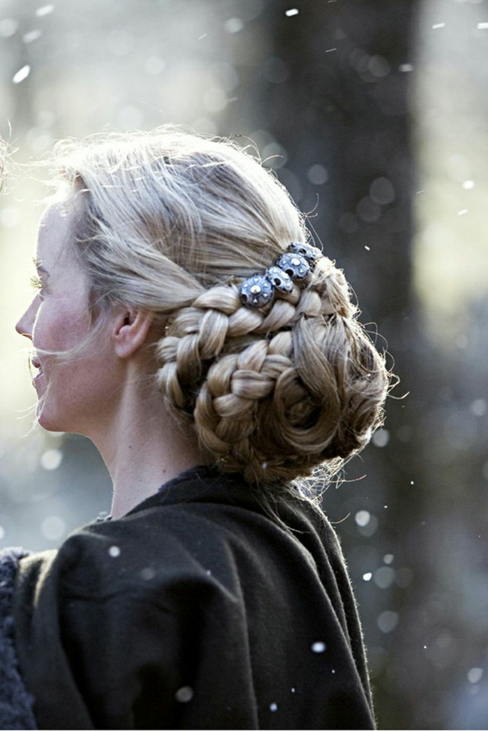 medieval braids, blonde braided hair, forming a voluminous bun at the back, decorated with silver ornaments, worn by woman in dark grey mantle
