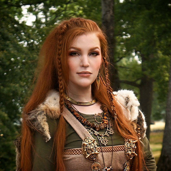 medieval braids, red-haired woman, long hair decorated with two braids, wearing a green and pale brown dress, with a fur cape, jewelry and ornaments from gold, amber and silver