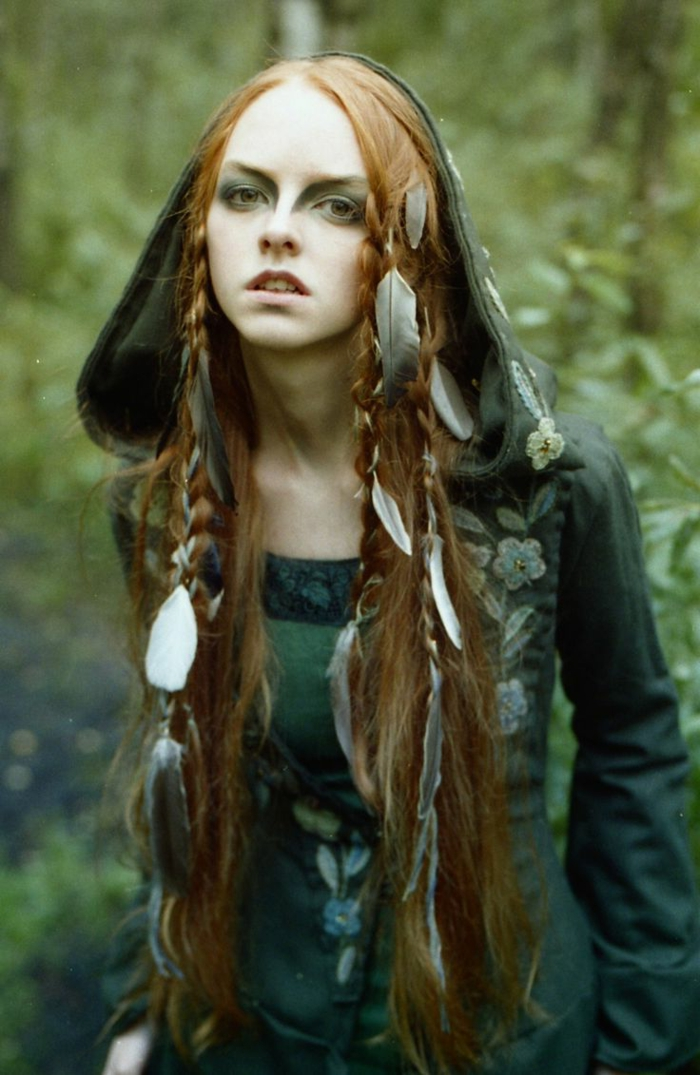 medieval braids, young woman wearing green embroidered dress with hood, long ginger hair, decorated with several braids, and many feathers, strong green eye makeup