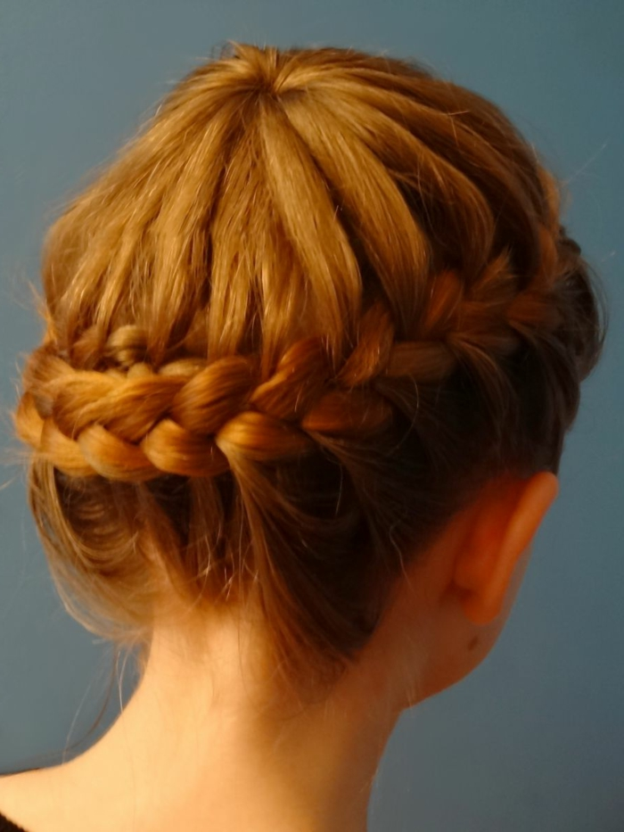 medieval hairstyles, close up of girl with ginger hair, woven into a side braid, going round her head