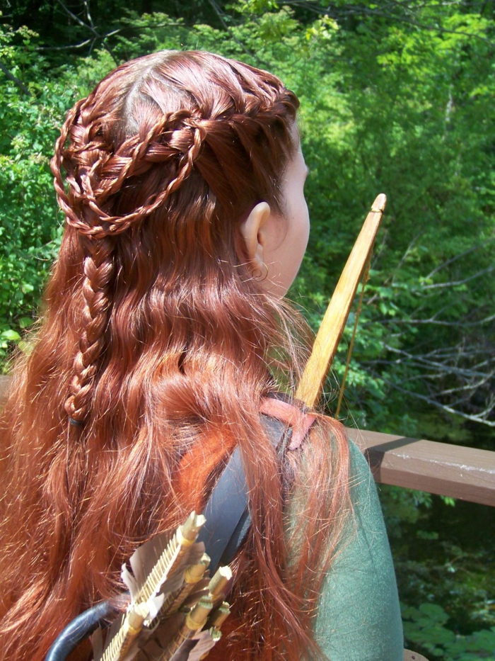 medieval hairstyles, girl holding wooden bow and arrows, with red partially braided hair, forming a complex pattern at the back of her head