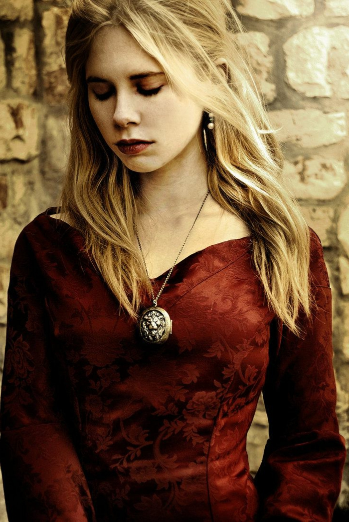 medieval times hair, young woman with red lipstick and dress, with floral embroidery, wavy blonde hair, and a chunky locket