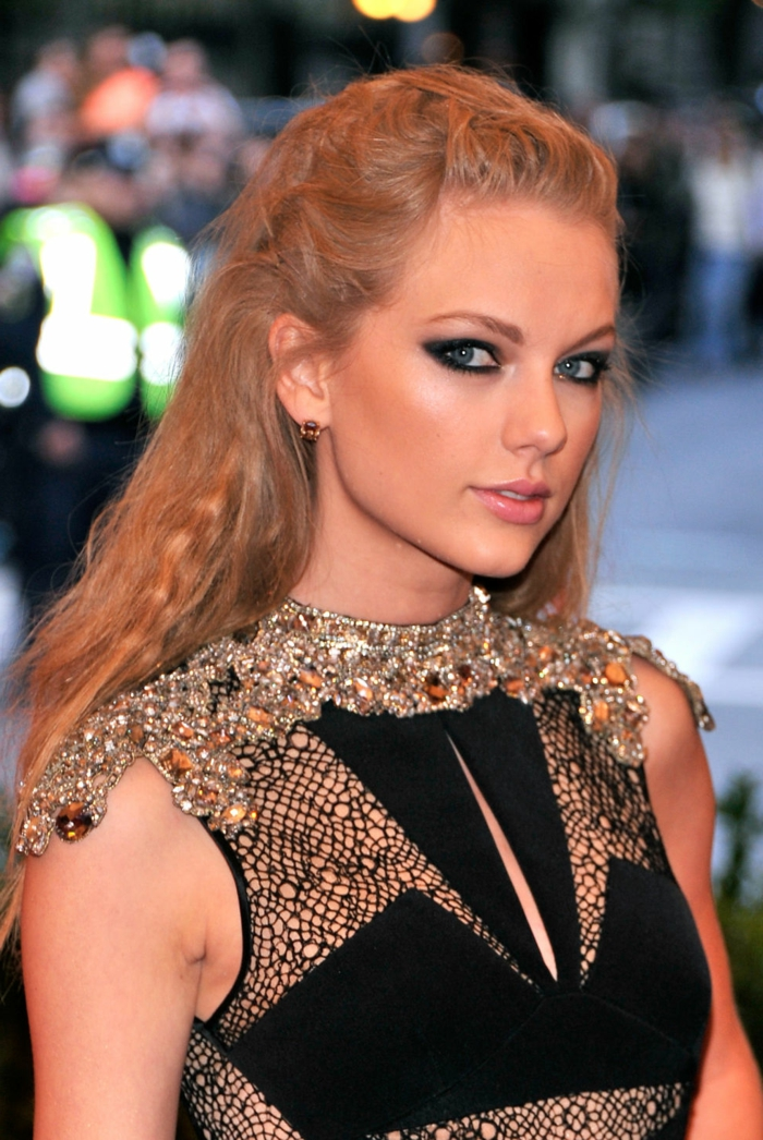 elizabethan hairstyles, taylor swift wearing a black dress, with mesh details and metallic decorations, her blonde hair woven in a messy, renaissance-like style