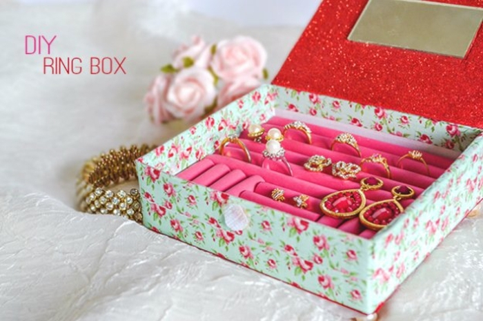 jewelry box in pale blue, with rose pattern outside, and pink and red inside, easy arts and crafts, various rings and earrings inside, barcelet and pink roses nearby