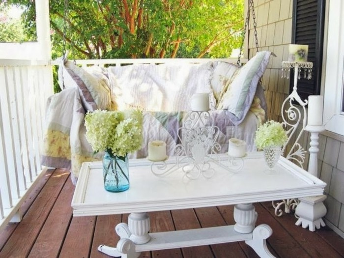 couch with throw and pillow in light, pastel colors, near ornate white rectangular table, with candle holder and vases, wooden floor and front porch décor