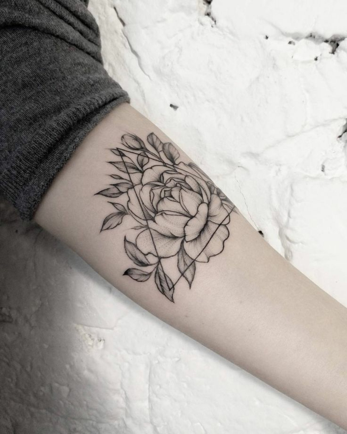 flower tattoo designs, close up of a person's arm, rolled up grey sleeve, rose tattoo decorated with triangular shape, all outlined in black ink