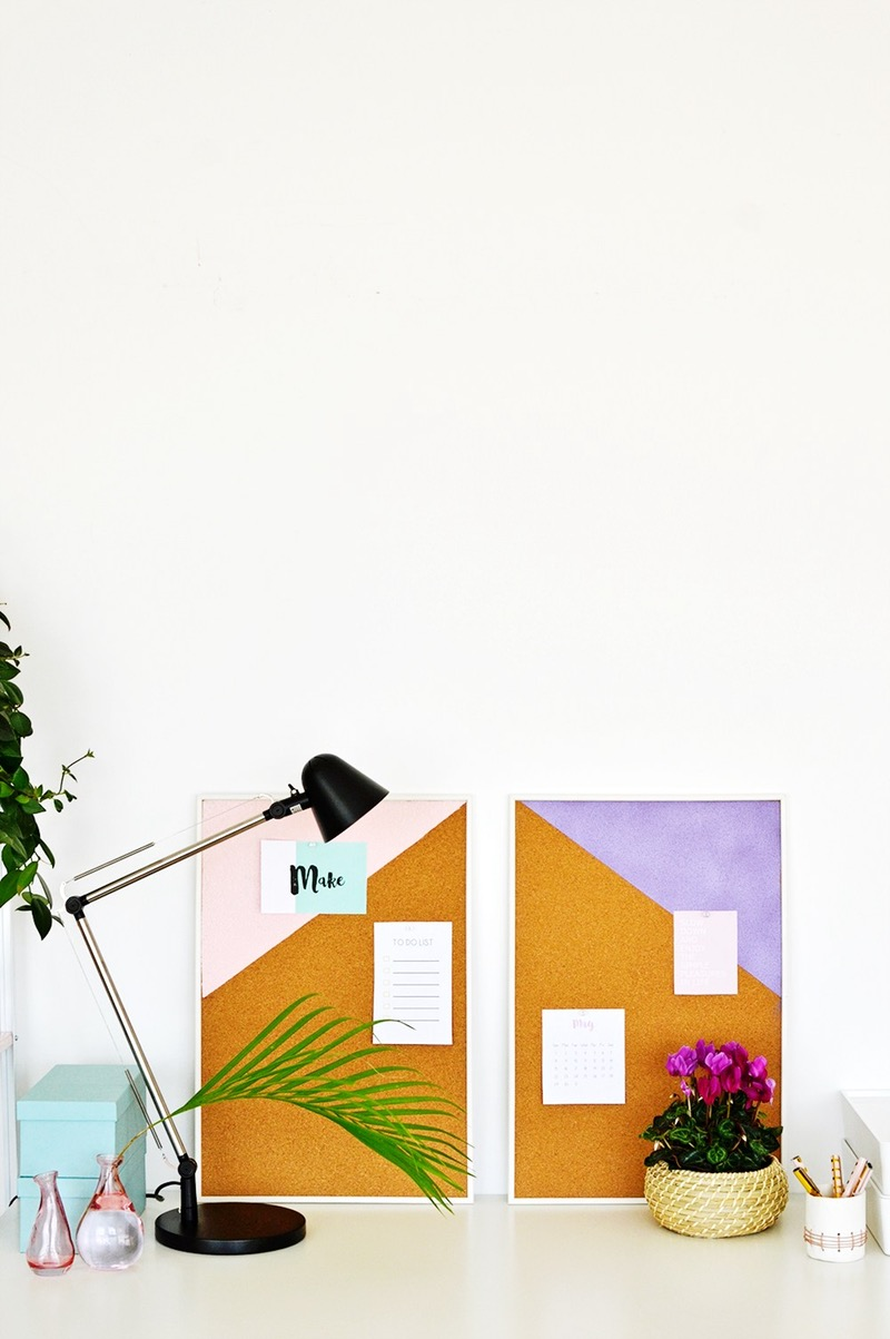 notice boards made of cork, partly painted n pale pink, or violet, with several pieces of paper pinned on them, plants and a desk lamp nearby