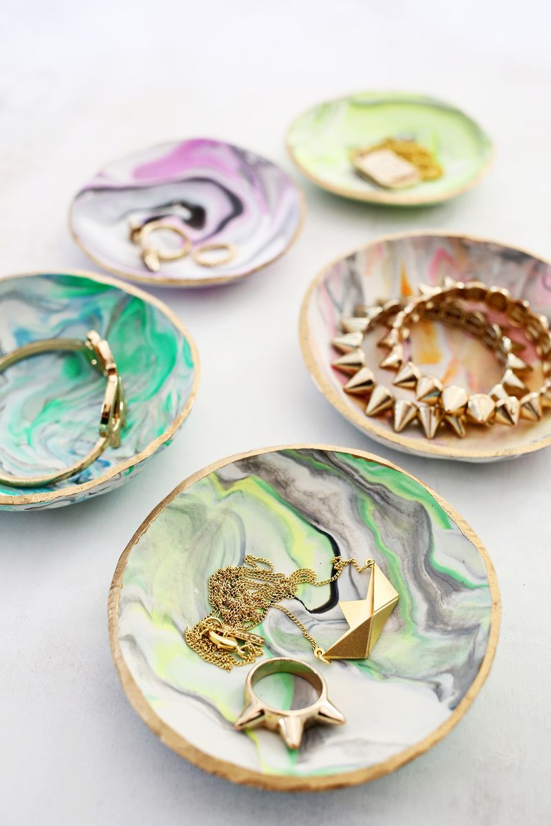 five small saucers, dyed in different psychadelic colors, containing rings, bracelets and pendants