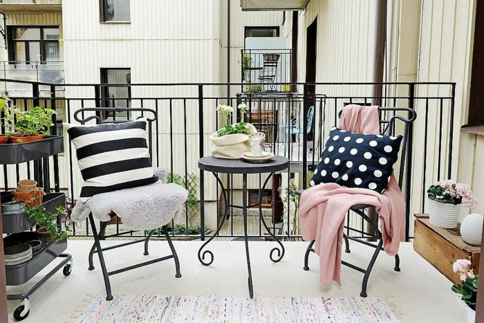 small round black metal table, and two matching chairs, each covered with a different throw and cushion, with shelves containing potted flowers nearby, front porch decorating ideas