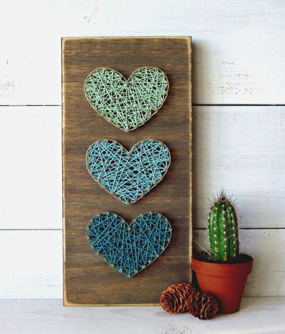 rectangular wooden board, decorated with three heartshapes, made with nails, and string in different shades of blue, easy arts and crafts, cactus plant nearby