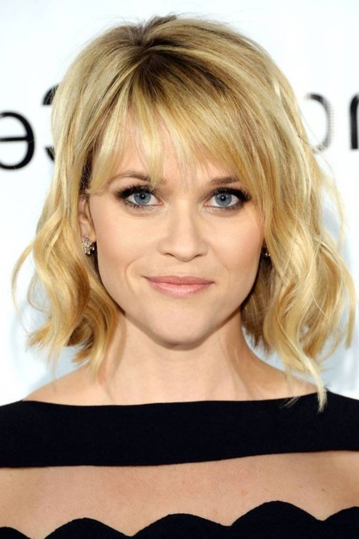 smiling reese witherspoon, wearing striped top, nude lipstick and dark mascara, with blonde shoulder length bob and bangs