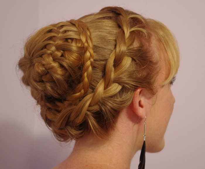 renaissance braids, braided blonde hair, with several layers of braids, forming a bun at the back, black feather earrings