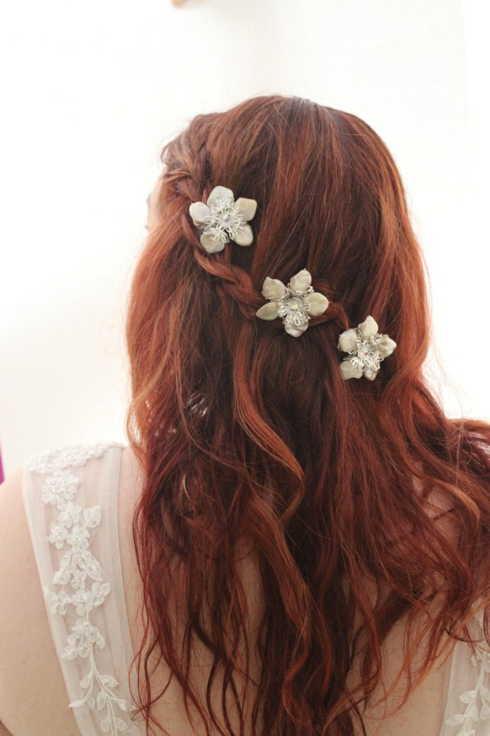 renaissance braids, messy and wavy red hair, with a single side braid, decorated with three white flower ornaments