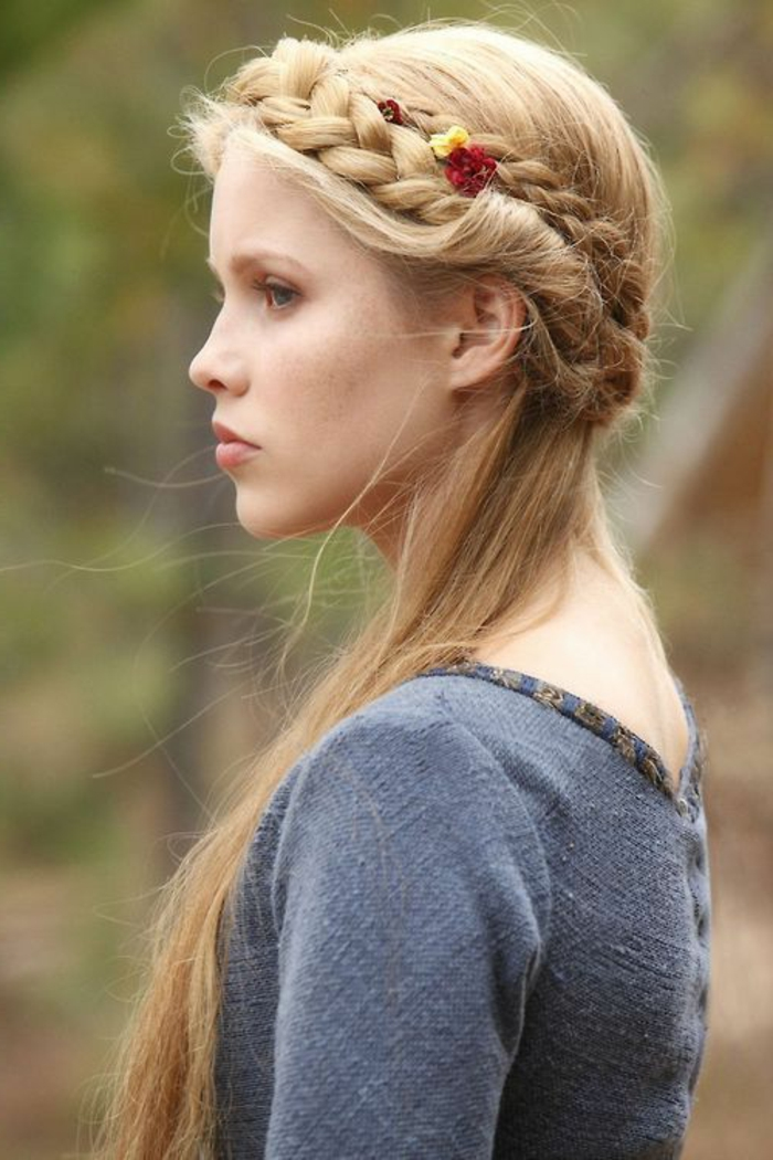 renaissance hairstyles, woman looking to one side, blue-grey rough fabric top, long straight blonde hair, woven into a crown-like braid, and decorated with flowers