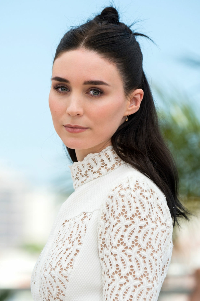 rooney mara, with dark hair parted in the middle, and small renaissance-inspired hair knot at the back, wearing white long-sleeved dress with lace details