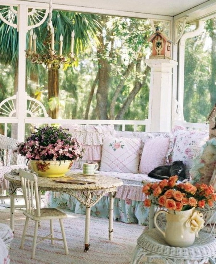 white round table with small chair, near couch with pale blue and pink cover, decorated with pale pink cushions, with frills and floral pattern, porch décor, many decorative objects