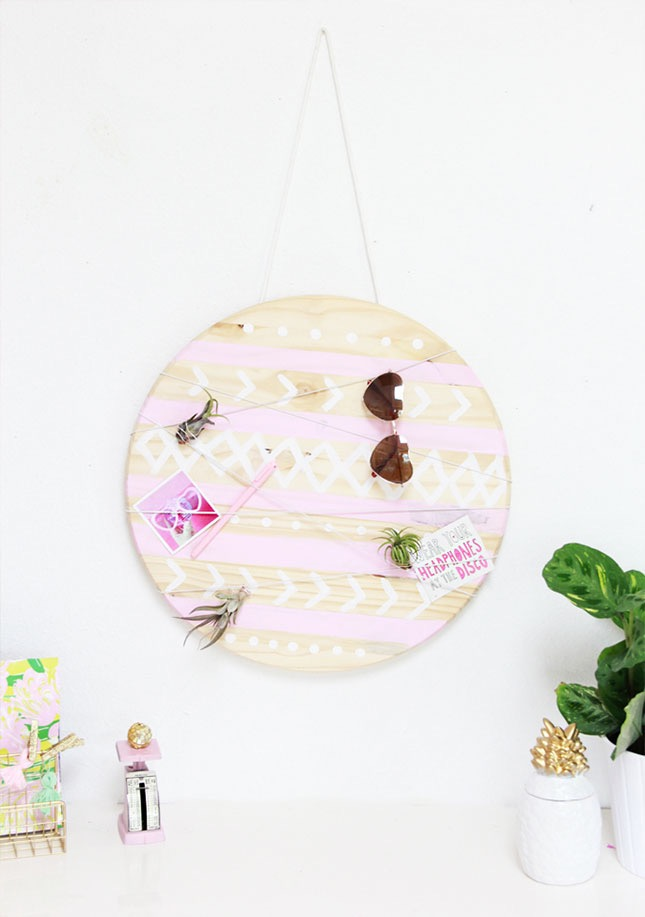 round wooden board on a wall, decorated with pale pink stripes, and white patterns, sunglasses and other items, hanging on it from a thread,