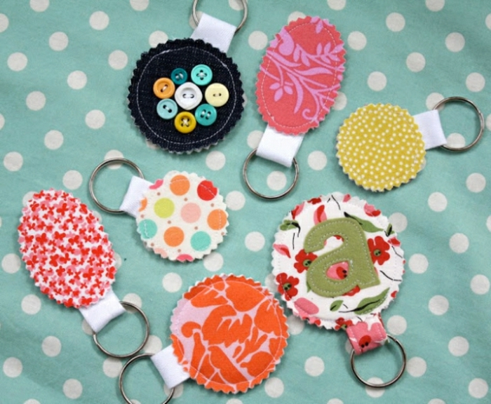 diy craft projects, seven keyrings, made from multicolored fabric, in different patterns, and metal rings, blue background with white polka dots