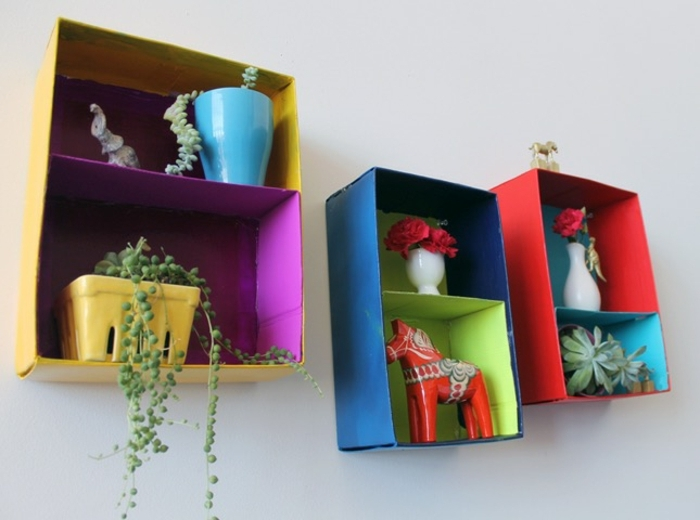 shelves made from carboard boxes, each painted in two different colors, yellow and purple, blue and green, or red and turquoise, homemade crafts