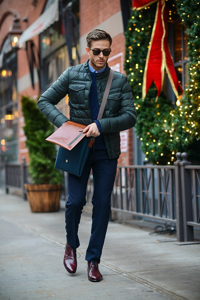 warm puffy down jacket in black, worn by young man in smart navy trousers, business casual dress code, with dark blue jumper, brown leather shoes, and brown and navy bag
