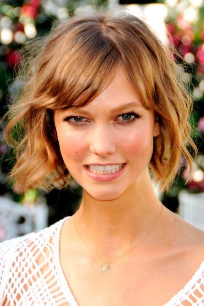 karlie kloss with curly, copper colored short bob, and side bangs, wearing white meshy top