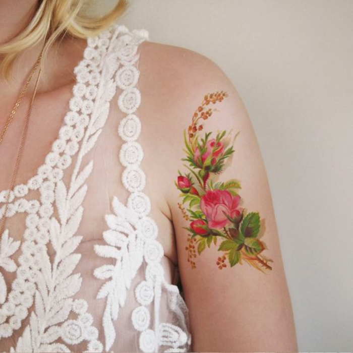 shoulder flower tattoos, blonde woman with sheer, white embroidered dress, a tattoo of several pink roses, with green leaves and other smaller plants, near her shoulder