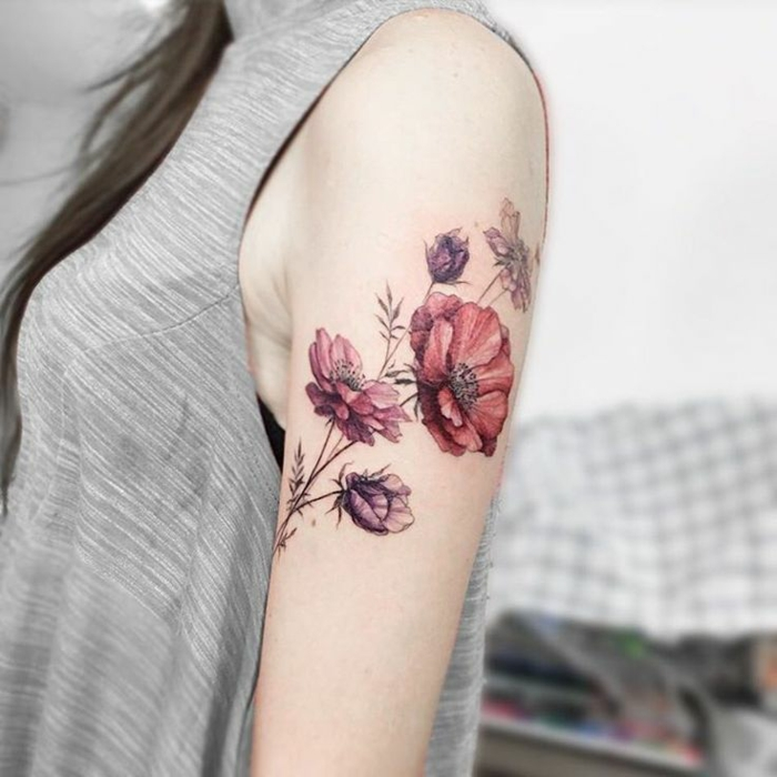shoulder flower tattoos, brunette woman with long hair, and pale grey top, with a watercolor effect tattoo of several poppies, in pale red and violet, on her upper arm