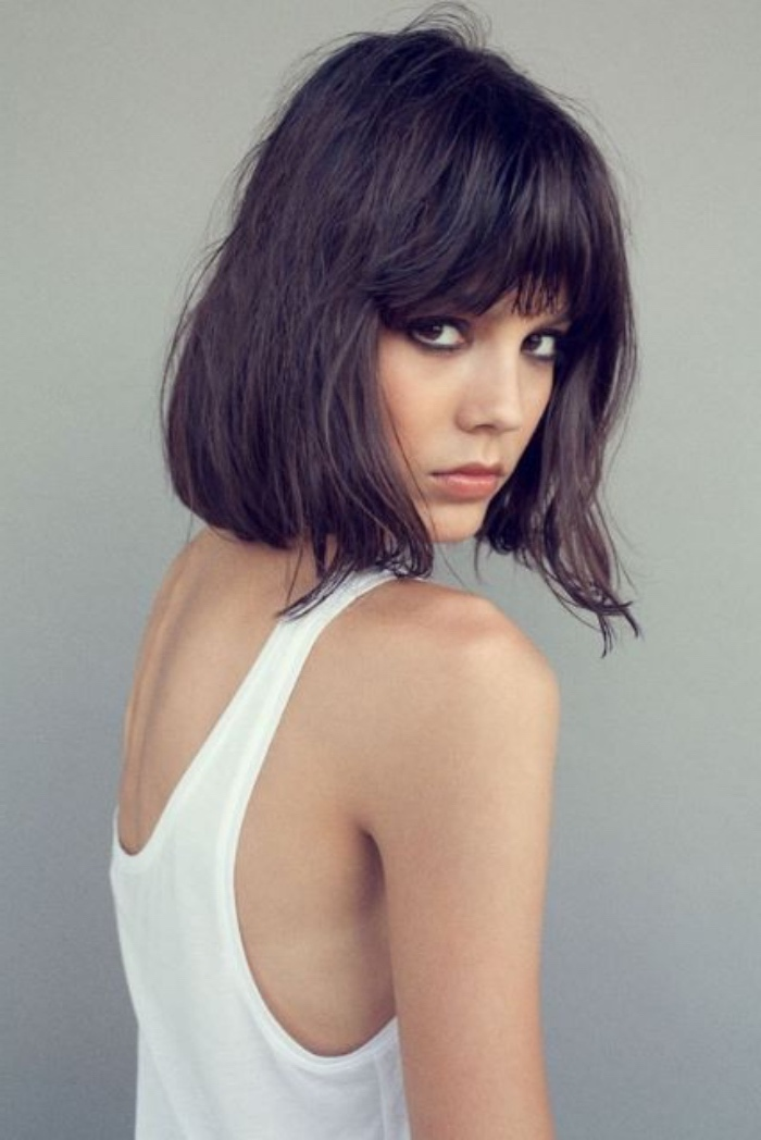 short bob haircuts, slim woman in white tank top, wearing messy dark hair with shaggy bangs
