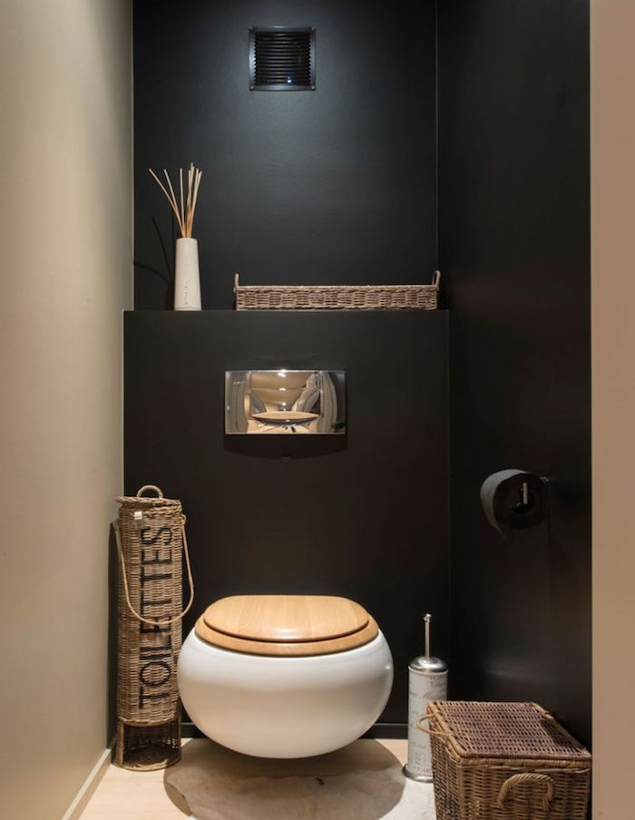 bathroom remodel, toilet with cream and black walls, containing oval white toilet seat with wooden lid, various whicker containers, black toilet paper