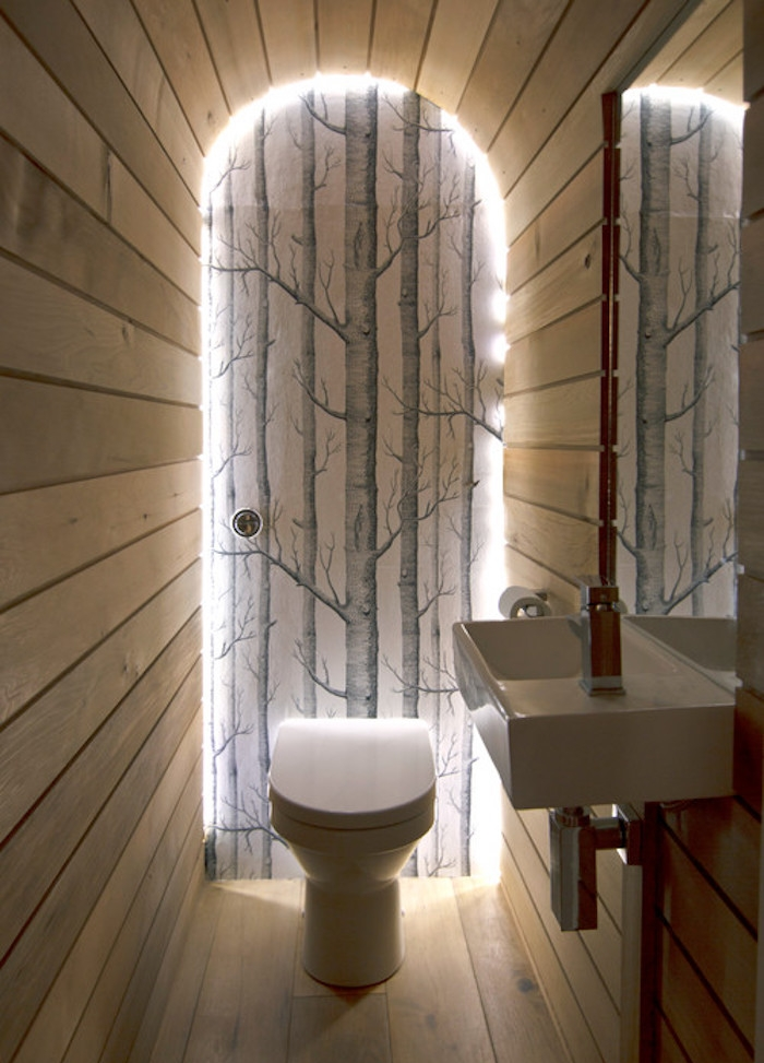 bathroom remodel, narrow toilet with wood plank-covered walls, ceiling and floor, one wall is decorated with a grey wallpaper, showing leafless grey painted trees, with backlighting, modern white toilet seat and sink