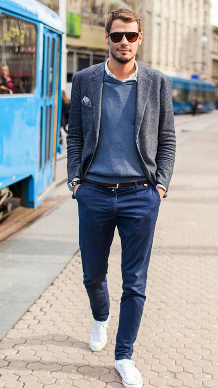 man with sunglasses, and hands in his pockets, wearing blue carrot pants, white sneakers, and a grey blazer, over blue jumper and white shirt, business casual attire