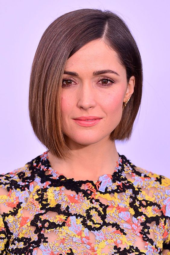 smooth and straight bob, slightly asymmetrical and with a side parting, worn by brunette actress, in a multicolored top