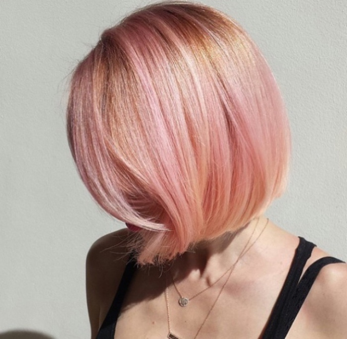 short hair colored in pink and pale orange, bob haircut, worn by woman in black strappy top