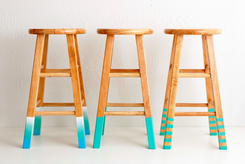 three bar stools, the tips of their legs have been painted, one in white and teal with ombre effect, one plain turquoise, one striped turquoise