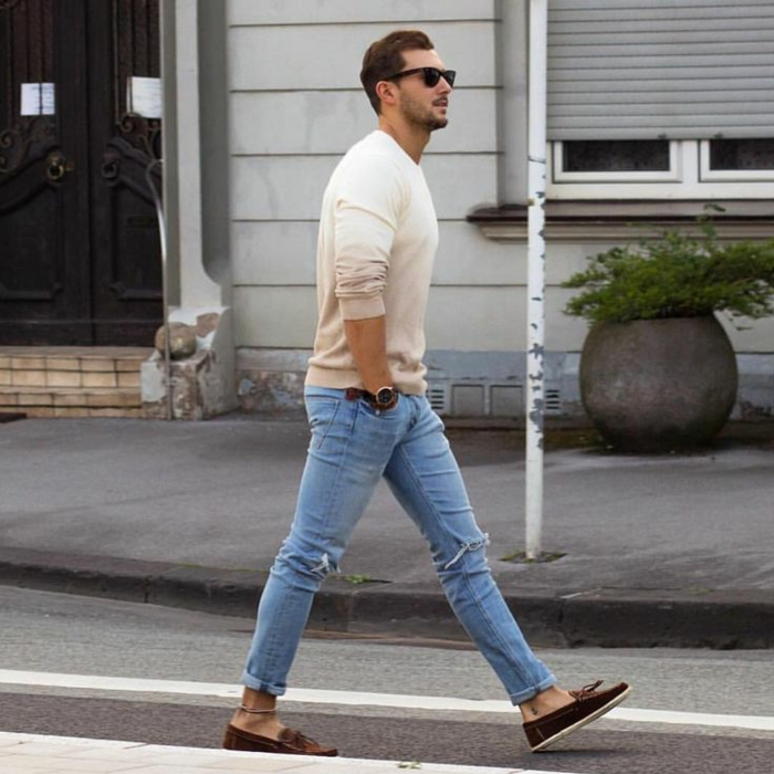 casual clothes for men, distressed pale blue jeans, worn with brown suede loafers, ombre effect jumper in white and beige, and sunglasses