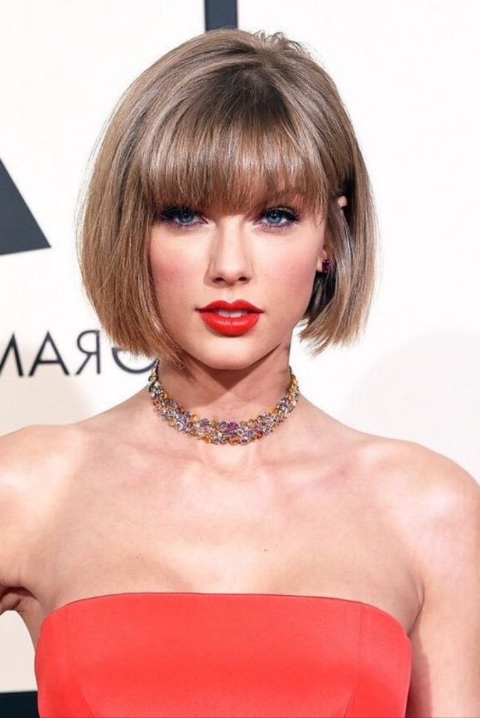 taylor swift wearing a pageboy haircut with bangs, coral red strapless top, bright red lipstick, collar necklace encrusted with gems