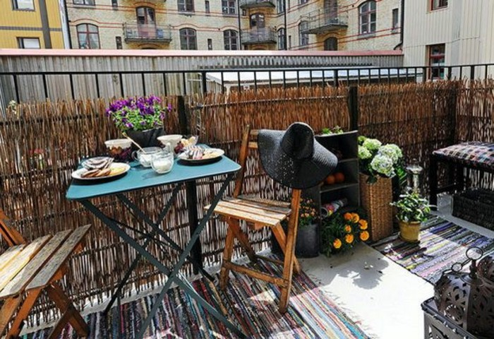 blue metal table set for breakfast, two wooden chairs, one decorated with black straw hat, flowers an house plants, front porch décor