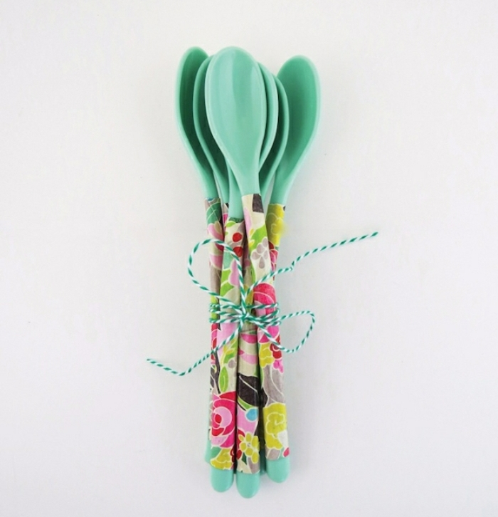 several turquoise colored spoons, fun and easy crafts, handles decorated with decoupage, tied together with blue and whte twisted string
