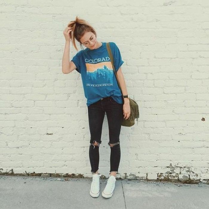 blonde woman with glasses and high ponytail, wearing teal blue t-shirt with print, half tucked into dark torn skinny jeans, with dark green tasseled bag, and white sneakers