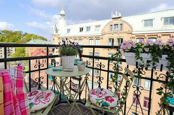 terrace with black ornate railings, with small round pale green table and matching chairs, decorated with cushions and pink blanket, potted plants and wooden laminate floor