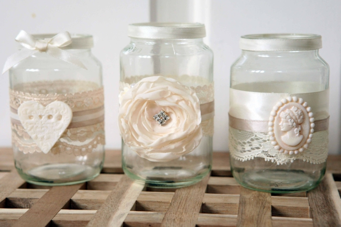 mason jar gifts, three clear jars, decorated with white lace and ribbon, one with a heart ornament, one with a faux flower, and one with a cream-colored brooch