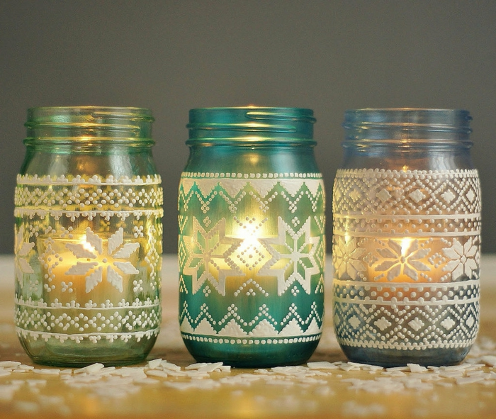 mason jar gifts, three jars in pale green, turquoise and blue, decorated with nordic sweater patterns, painted in white, and lit from within