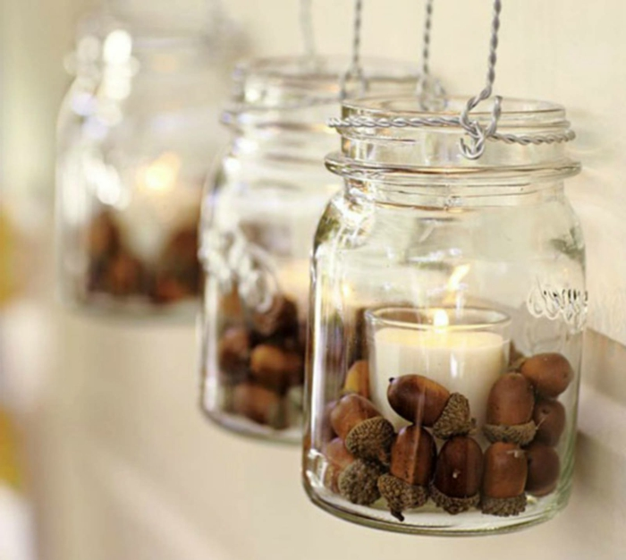diy mason jar, three mason jars, with handles made of twisted wire, containing acorns and glasses with lit candles